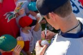 Baseball player signing autographs before a game
