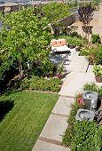 Oasis de patio trasero y retiro suburbano con flores, silla de salón y patio