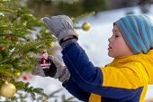 Boy Hanging Christmas Decorations On A Christmas Tree Outside. Child Holding A Santa Claus Holiday O poster