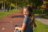 Happy Child Rides A Bike On Bike Path. Cyclist Child Or Teenager Girl Enjoys Good Weather And Cyclin poster