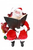 Closeup of Santa Claus (that jolly old elf that  lives at the North Pole) reading and writing in the