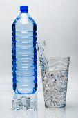 Постер, плакат: бутылка минеральной воды и стакан со льдом