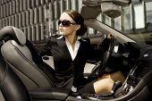 beautiful brunette businesswoman driving a cabrio car