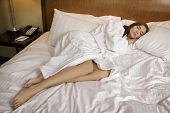 Beautiful brunette woman is resting on white bed
