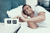 Cheerful Man Awakes And Pulls Alarm Off In Morning. Smiling Young Person In Good Mood Lying In Bedro poster