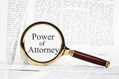 Power Of Attorney Concept - Paperwork Representing A Power Of Attorney, With A Magnifying Glass Over poster
