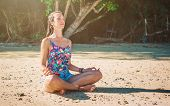 Fit Woman Relaxing And Practicing Yoga On The Summer  Beach. Relax And Meditate Concept poster