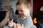 Cute Boy With Down Syndrome Playing With Dad On In Home Living Room poster