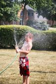 Young boy gets relief from the heat by spraying himself with a hose