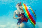 Beautiful woman underwater with a rainbow umbrella