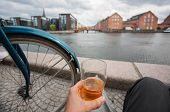 Cityscape With Water Channel, Old Buildings And Relaxed Visitor Of Copenhagen With Beer In Hand, Den poster