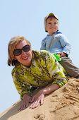 familia feliz de niño sentado a horcajadas sobre su madre en la arena