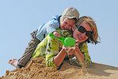 familia feliz de niño y la madre jugando con la arena en la playa