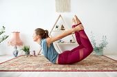 fitness, people and healthy lifestyle concept - young woman doing bow pose at yoga studio poster