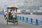 CHENGDU, CHINA - SEPTEMBER 16: Pedicab on the special lane of the carriageway as a result of a large amount of bicycle and scooters on roads on  September 16, 2006 in Chengdu, Sichuan, China.