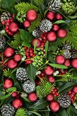 Christmas flora with holly, fir, ivy, mistletoe and pine cones with red bauble decorations forming a poster