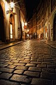 stock photo of cobblestone  - mysterious narrow alley with lanterns in Prague at night - JPG