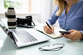 Female Editor Writing Notes In Diary With Laptop And Dslr Camera On Desk poster
