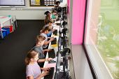 Line Of High School Students Working at Screens In Computer Class With Female Teacher In Background  poster