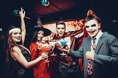 Friends In Halloween Costumes Drinking Cocktails. Group Of Young Happy People Wearing Costumes At Ha poster
