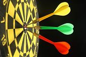 Three colourful darts in the bullseye.