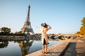 Young Woman Tourist Enjoying Landscape View On The Eiffel Tower With Beautiful Reflection On The Wat poster