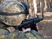 stock photo of hider  - The soldier aiming the target in the woodland  - JPG
