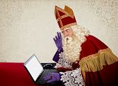Sinterklaas looking on notebook. Vintage look. Dutch character of Santa Claus poster