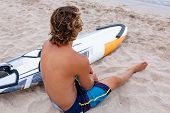 Handsome Man Sits On The Beach With White Blank Surfing Board Wait For Wave To Surf Spot At Sea Ocea poster