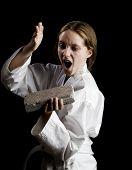 Young Girl Karate Chopping A Brick
