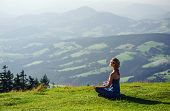 stock photo of legs crossed  - Young woman meditating outdoors - JPG