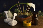image of vedic  - An arrangement of turmeric spice oil bowl and bottle and massage poultice boluses used in Ayurveda massage with an exotic flower and incense burning in the background - JPG