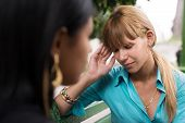 Woman Having Headache While Talking With Friend