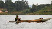 African Man Paddles Dugout Canoe