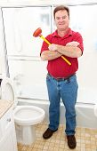 Plumber or homeowner holding a plunger and standing in a modern bathroom.