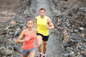 Runners couple running on trail in cross country run outdoors training on Hawaii, Big Island for mar