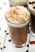 Closeup image of ice coffee with whipped cream and coffee beans