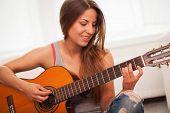 Young beautiful caucasian woman in casual playing guitar