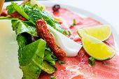 Carne fresca de carne crua fatiadas com folhas de alface na mesa