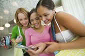Happy multiethnic young women looking at cell phone picture in the clothing store
