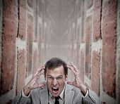 Angry businessman in a dead end in the middle of a bricks corridor