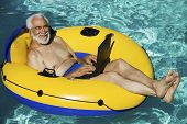 Portrait of a happy senior man lying on inflatable raft using laptop in swimming pool