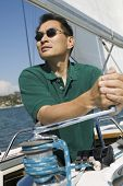 Asian man raising sail on the sailboat against clear sky