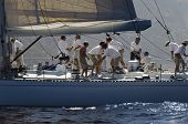 stock photo of work crew  - Side view of crew members working on sailboat - JPG