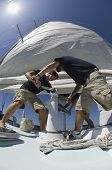 Low angle view of crew members operating windlass on yacht