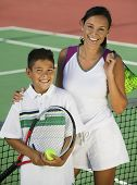 Portrait of happy mother and son with balls and racquet by the net on tennis court