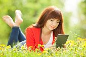Happy woman with tablet in the park