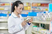 chinese pharmacist chemist woman choosing tablets in china pharmacy drugstore