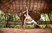 foto of ashtanga vinyasa yoga  - Yoga Parsvakonasana pose by fit man in white trousers on the drought earth in yoga shala Varkala Kerala India - JPG