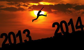 stock photo of happy new year 2013  - Silhouette of a man jumping from 2013 towards 2014 year at sunset - JPG